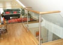 Treppengeländer im Innenbereich mit Pfosten aus Edelstahl und Glasfüllungen, Holzhandlauf