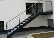 Außentreppe mit Geländer aus Edelstahlseilen und einem Abschlusshandlauf aus Edelstahl