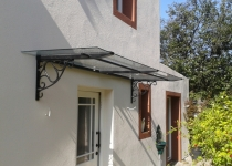 Haustürüberdachung aus Glas und Messing