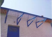 Haustürüberdachung aus Glas mit blauen Stützen