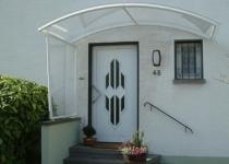 Bogenförmige Haustürüberdachung mit seitlichem Wetterschutz